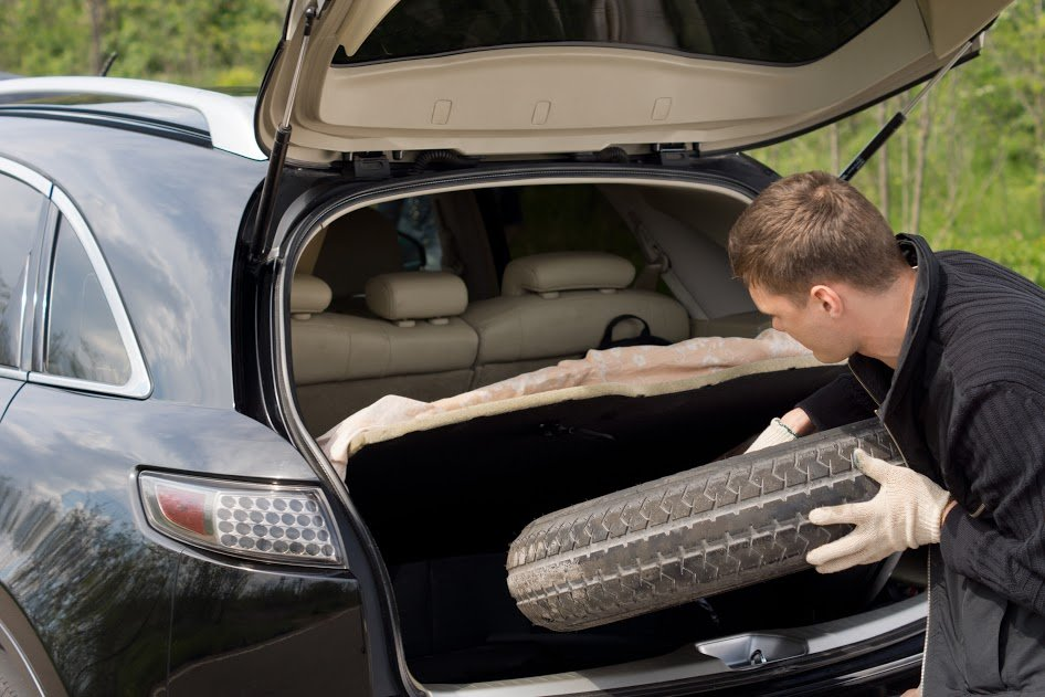 Pulling a spare tire out of a hatchback vehicle - Chelsee's AC & Brake Emporeum